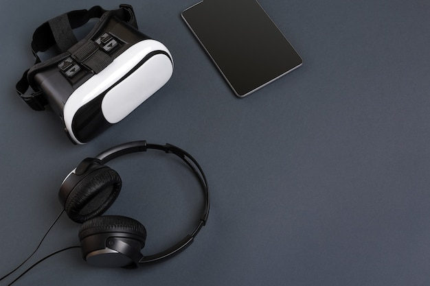 Occhiali per realtà virtuale e tablet con cuffie su sfondo grigio vista dall'alto
