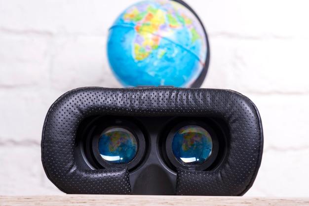 Occhiali per realtà virtuale con il riflesso del modello del pianeta negli oculari