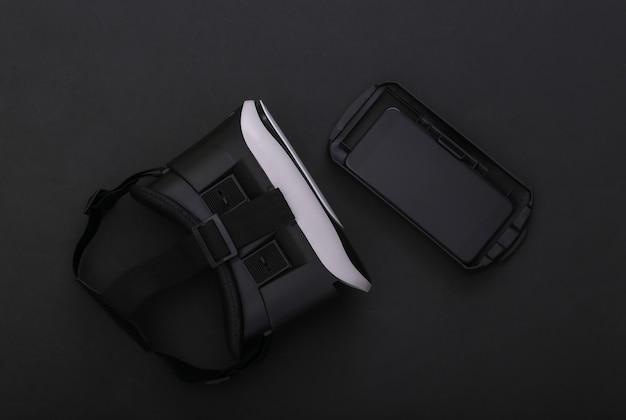 Cuffie e smartphone per realtà virtuale su sfondo nero. gadget moderni. vista dall'alto