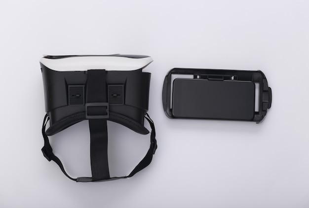 Cuffie e smartphone per realtà virtuale su sfondo bianco. gadget moderni. vista dall'alto