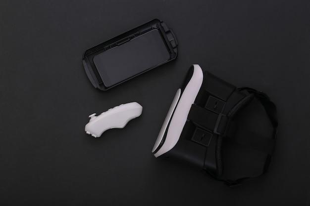 Cuffie per realtà virtuale con joystick e smartphone su sfondo nero. gadget moderni. vista dall'alto