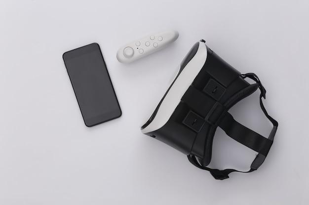 Cuffie per realtà virtuale con joystick e smartphone su sfondo bianco. vista dall'alto. scuotila