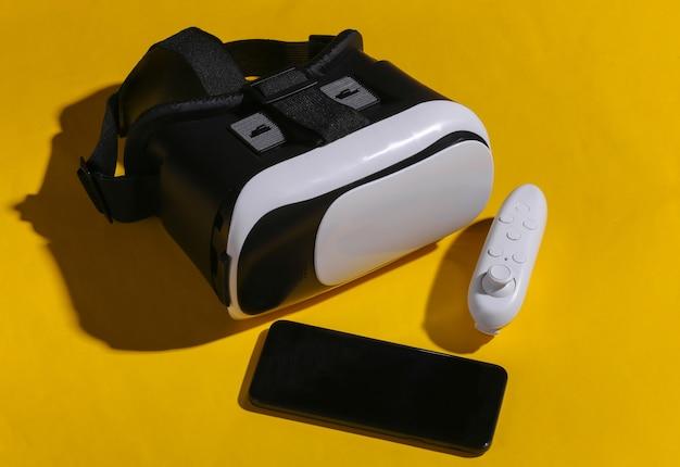 Cuffie per realtà virtuale con joystick e smartphone su sfondo giallo con ombra. gadget moderni