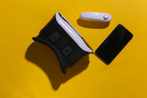 Cuffie per realtà virtuale con joystick e smartphone su sfondo giallo con ombra. vista dall'alto. scuotila