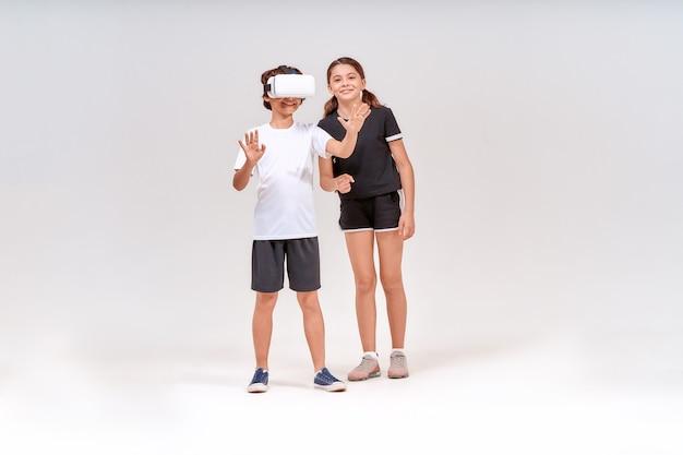 Realtà virtuale e sport due adolescenti eccitati che indossano occhiali d e una ragazza carina in piedi isolata