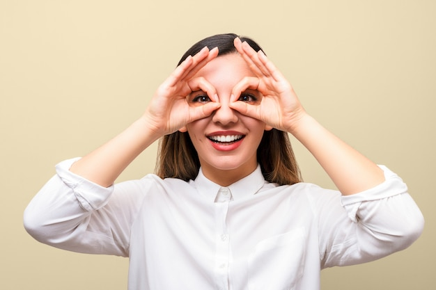 Aiuti alla vista. giovane donna che tiene le mani sugli occhi imitando gli occhiali e sorridendo allegramente