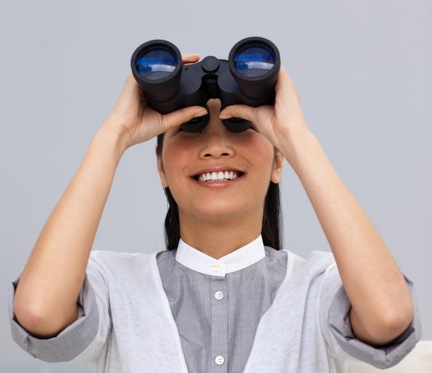 Donna di affari asiatica visionaria che osserva tramite il binocolo