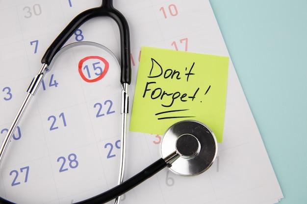 Visita il promemoria del medico su una nota adesiva e uno stetoscopio su un calendario