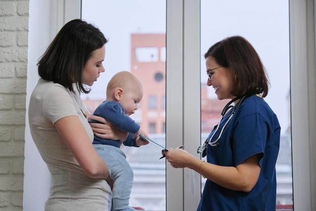 Visita madre con bambino in ospedale, parlando medico pediatra e giovane donna
