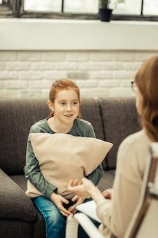 Visita dallo psicologo. piacevole ragazza sorridente mentre è seduta con un cuscino sul divano