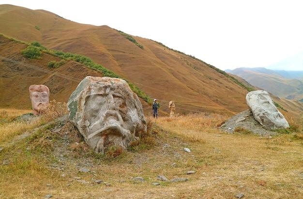 Visitatore nel campo delle gigantesche sculture di testa nel villaggio di sno kazbegi georgia