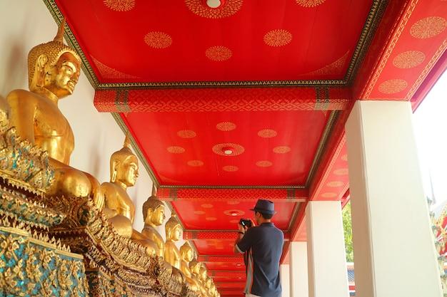 Visitatore che scatta foto di un gruppo di buddha seduti in un tempio a bangkok