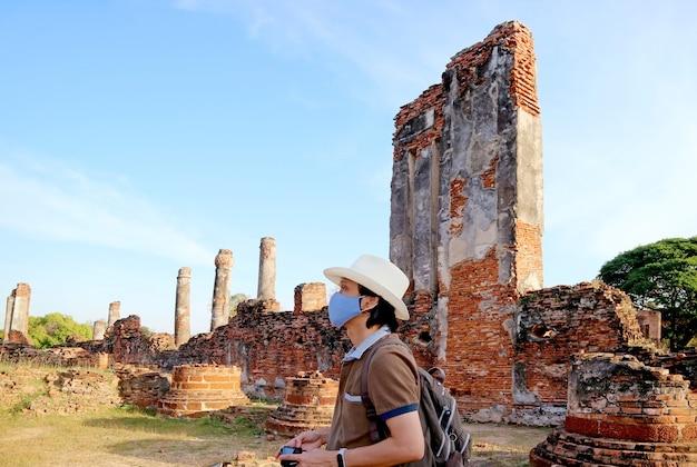 Visitatore che indossa la maschera facciale durante una visita al wat phra si sanphet in mezzo al covid19 ayutthaya thailandia