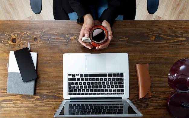 Vista superior de escritorio de madera en casa y unas manos tomando una taza de cafe con un ordenad