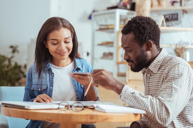 Dati vitali. bellissima giovane donna che scatta una foto di documenti con i risultati della ricerca mentre ne discute con il suo piacevole collega in un caffè