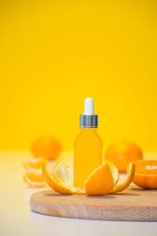 Flacone cosmetico di siero di vitamina c in buccia di mandarino con pezzi di arancia su sfondo giallo con spazio di copia.
