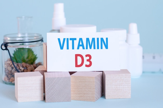 Parole di vitamina d3 scritte su scheda medica bianca, con fiore verde, pillole mediche e blocchi di legno.
