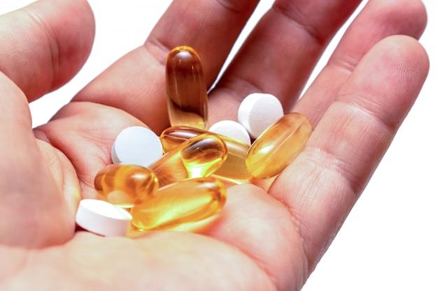Le pillole gialle dell'olio di pesce della vitamina e omega 3 in vitamine di una mano mettono in mostra la nutrizione sana sulla fine isolata fondo bianco su