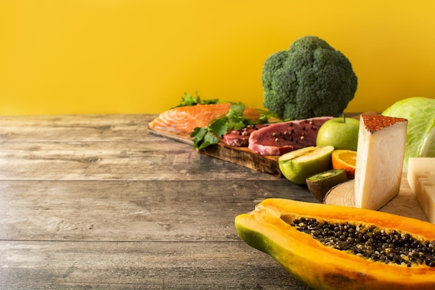 Vitamina a negli alimenti con frutta, verdura, formaggio, pesce e carne su tavola di legno e sfondo giallo