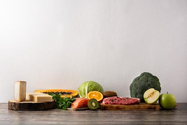 Vitamina a negli alimenti con frutta, verdura, formaggio, pesce e carne sulla tavola di legno