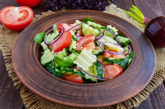 Insalata di vitamine con cetrioli, pomodori, cipolla viola e formaggio in una ciotola di argilla sul tavolo di legno
