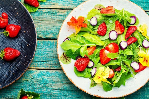 Insalata vitaminica con fragole, spinaci, nasturzio e rucola. insalata verde vegana. vista dall'alto su tavola di legno