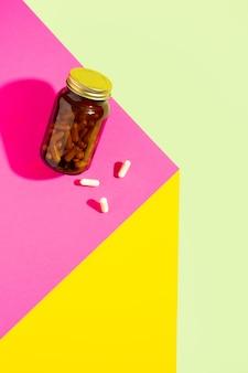 Capsule di vitamina valeriana sonniferi in bottiglia di vetro su sfondo blu rosa giallo con trendy