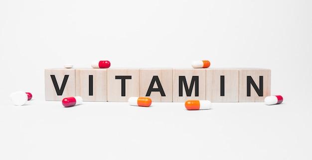 Vitamina la parola sui cubi di legno, i cubi stanno su una superficie bianca riflettente.