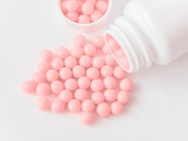 Vitamine. antidepressivi. compresse di farmaci antivirali. round rosa pillole sane e bottiglia di pillola su sfondo bianco. globuli omeopatici, medicina omeopatica alternativa.