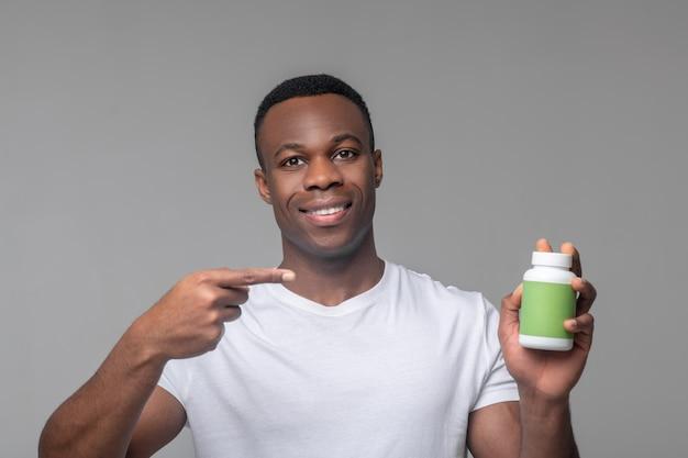 Vitamine, benefici. sorridente giovane afroamericano in maglietta bianca che punta con il dito sul pacchetto di vitamine in mano in piedi in studio