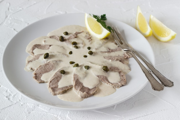 Il vitello tonnato è un piatto tradizionale italiano su un tavolo bianco.