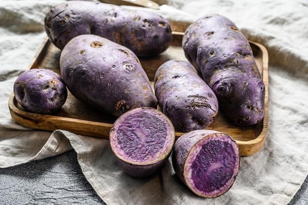 Vitelotte di patate crude su un tagliere. sfondo grigio. vista dall'alto