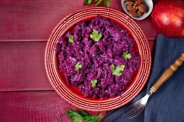 Vivace composizione con insalata di cavolo cappuccio vegano viola sulla tavola rossa. vista dall'alto