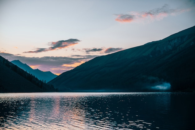 Il vivido cielo all'alba si riflette nel puro lago alpino vicino alle sagome di montagna all'alba