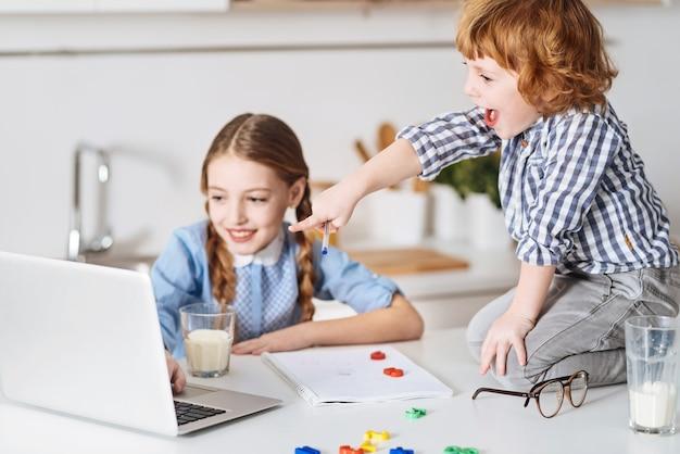 Esempi vividi. fratelli divertenti e simpatici che guardano alcuni video utili sul laptop mentre imparano nuove formule matematiche e si godono il loro tempo insieme