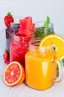 Bevande frullate fresche vivaci in barattoli di vetro con ingredienti sul tavolo bianco