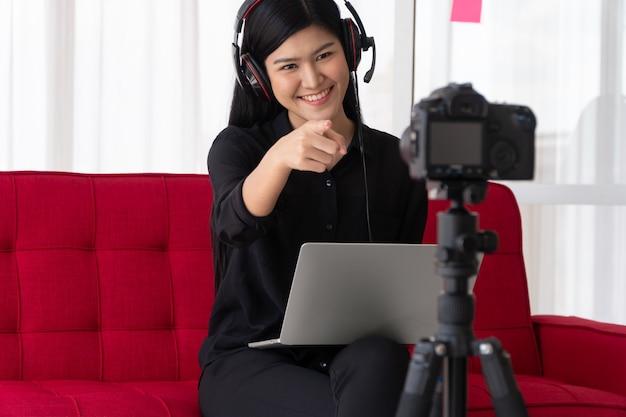Vlog influencer blogger donna asiatica seduta sul divano di casa e registrando video blog per insegnare e allenare i suoi studenti o iscritti. concept del creatore di contenuti online per un nuovo stile di vita