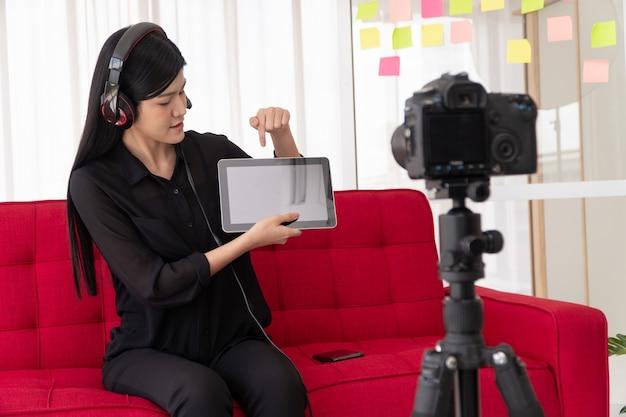 Vlog donna asiatica blogger influencer seduta sul divano di casa e registra video blog per insegnare e istruire i suoi studenti