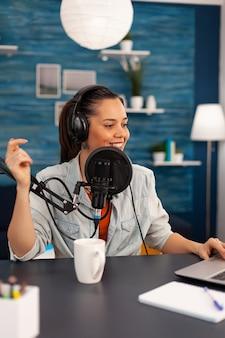 Vlogger guarda un laptop mentre chiede al suo pubblico di iscriversi al suo canale youtube. talk show di registrazione di influencer digitali utilizzando attrezzature moderne in podcast home studio