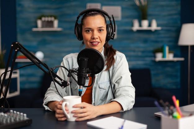 Vlogger invia messaggi al suo pubblico mentre realizza podcast in home studio per i social media. blogger che registra un talk show online utilizzando le cuffie, un microfono professionale che guarda la telecamera durante la trasmissione.