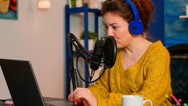 Vlogger che registra podcast utilizzando il microfono a casa studio utilizzando tecnologie per la creazione di contenuti per blogger e influencer