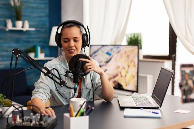 Vlogger che registra video blog con attrezzature moderne in podcast home studio. nuova star dei media che guarda la telecamera per la trasmissione digitale e si diverte a usare la tecnologia per connettersi con il pubblico