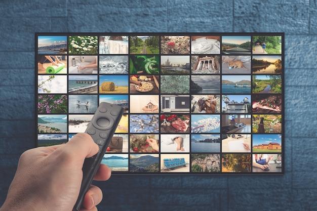 Servizio vod sul concetto di streaming televisivo tv uomo che tiene il telecomando con molte icone