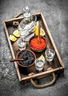 Vodka in una bottiglia con caviale nero e rosso. su fondo rustico.