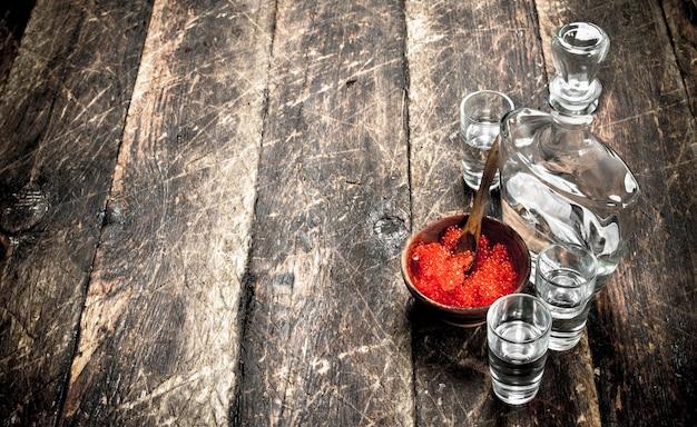 Vodka in una bottiglia con caviale nero e rosso. sullo sfondo di legno.