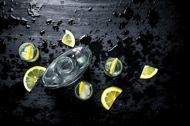 Vodka in bicchieri con limone e ghiaccio. sulla lavagna nera.