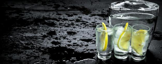 Vodka in bicchieri con limone e ghiaccio sulla lavagna nera.