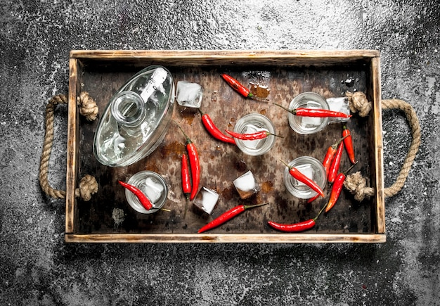 Colpi di vodka con peperoncino su un vassoio di legno. su fondo rustico.