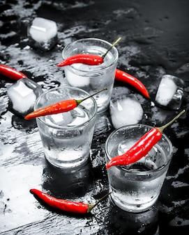 Colpi di vodka con peperoncino piccante e ghiaccio sulla lavagna nera
