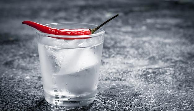 Colpi di vodka con peperoncino. su fondo rustico.